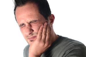 grimacing man holding jaw