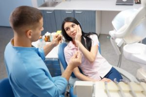 Woman at dentist holding jaw